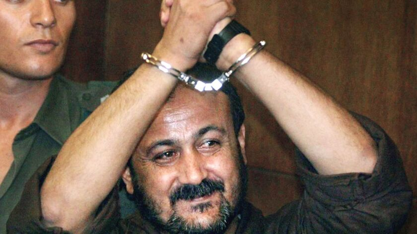 Jailed Palestinian uprising leader Marwan Barghouti raises his handcuffed hands as he enters the courtroom for the opening day of his trial at Tel Aviv's District Court, in this photo taken Aug. 14, 2002.