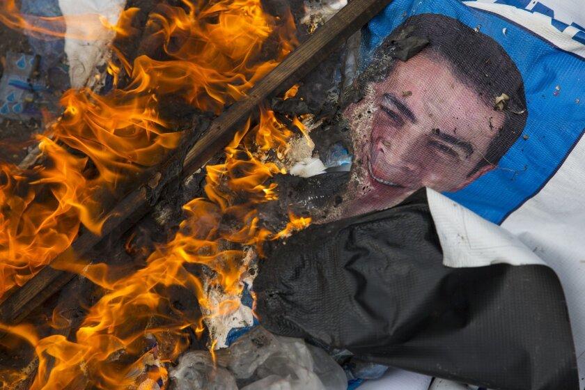 A campaign poster of Honduran President Juan Orlando Hernandez burns.
