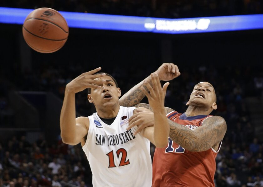 San Diego State's Trey Kell (12) and St. John's D'Angelo Harrison (11) battle for a rebound during the first half of an NCAA tournament college basketball game in the Round of 64 in Charlotte, N.C., Friday, March 20, 2015. (AP Photo/Gerald Herbert)