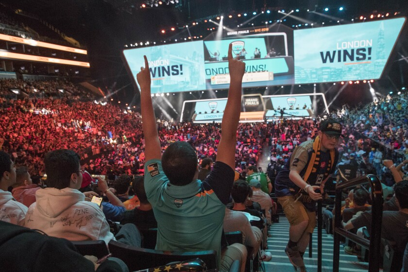 FILE - In this July 28, 2018, file photo, London Spitfire fan Rick Ybarra, of Plainfield, Ind., reacts after London won the second game against the Philadelphia Fusion during the Overwatch League Grand Finals competition at Barclays Center in New York. The Overwatch League took another step in its ambitious vision when franchises in Dallas and New York hosted season-opening matches last weekend. They were the first of 52 scheduled events on OWL's home-and-away calendar requiring teams to visit host arenas for all 20 teams spanning Europe, North America and Asia. (AP Photo/Mary Altaffer, File)
