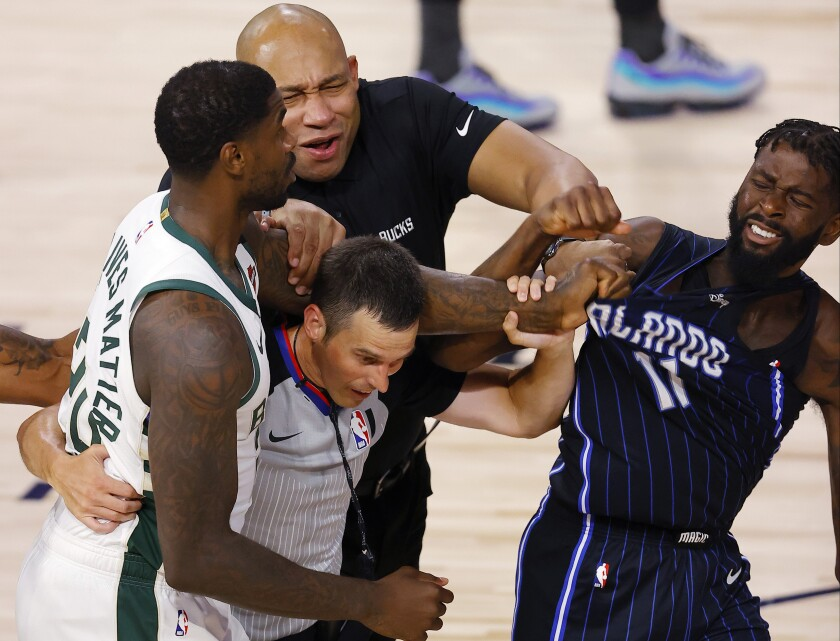 Bucks forward Marvin Williams (20) grabs Magic forward James Ennis III (11) as officials try to separate them during Game 3.
