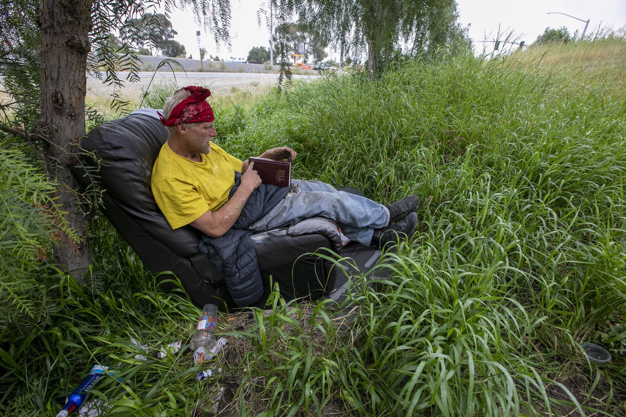Jacob Nilsen, who is homeless, sat in a chair next to Interstate 805 in National City reading a Bible on Thursday. Outreach workers have been unable to convince him to go to a shelter.