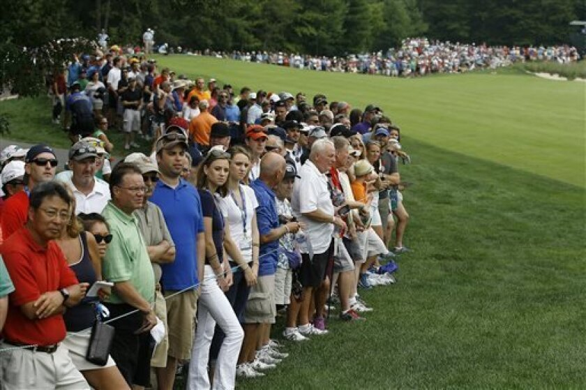 The gallery gathers to watch Phil Mickelson, Tiger Woods and Adam Scott, not pictured, on the second hole during the second round of the Deutsche Bank Championship golf tournament in Norton, Mass., Saturday, Aug. 31, 2013. (AP Photo/Stew Milne)