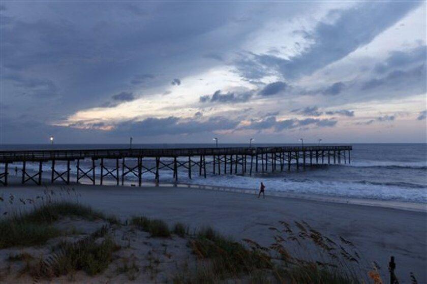 A woman walks on the beach near a pier slightly damaged after Hurricane Earl brushed the North Carolina coast in Atlantic Beach, N.C., Friday, Sept. 3, 2010. (AP Photo/Chuck Burton)