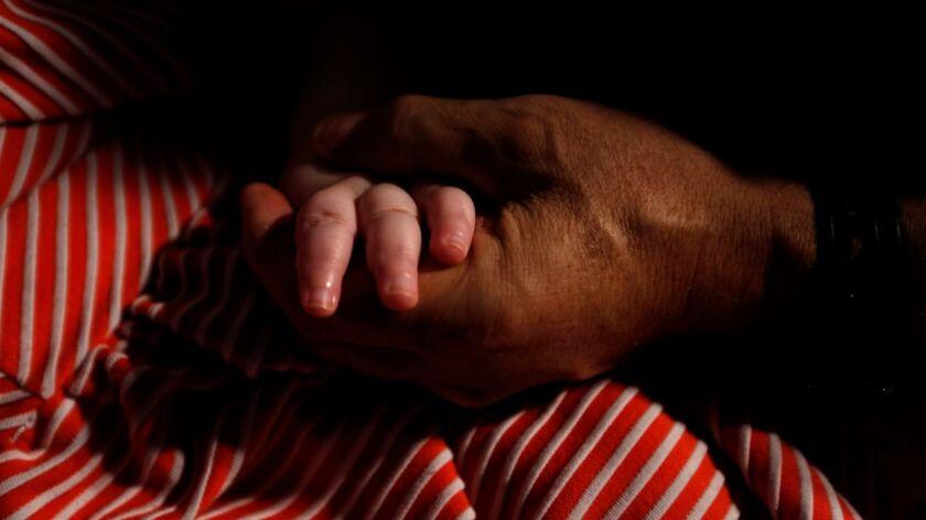 Mohamed Bzeek sostiene la mano de su hija de seis años de edad, que nació con una rara malformación cerebral y no puede ver, oír o hablar. Bzeek cuida hace más de dos décadas a niños en el sistema de adopción con enfermedades terminales (Genaro Molina / Los Angeles Times).