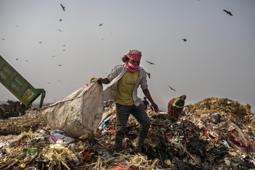 A man carrying a bag walks atop a huge mount of trash.