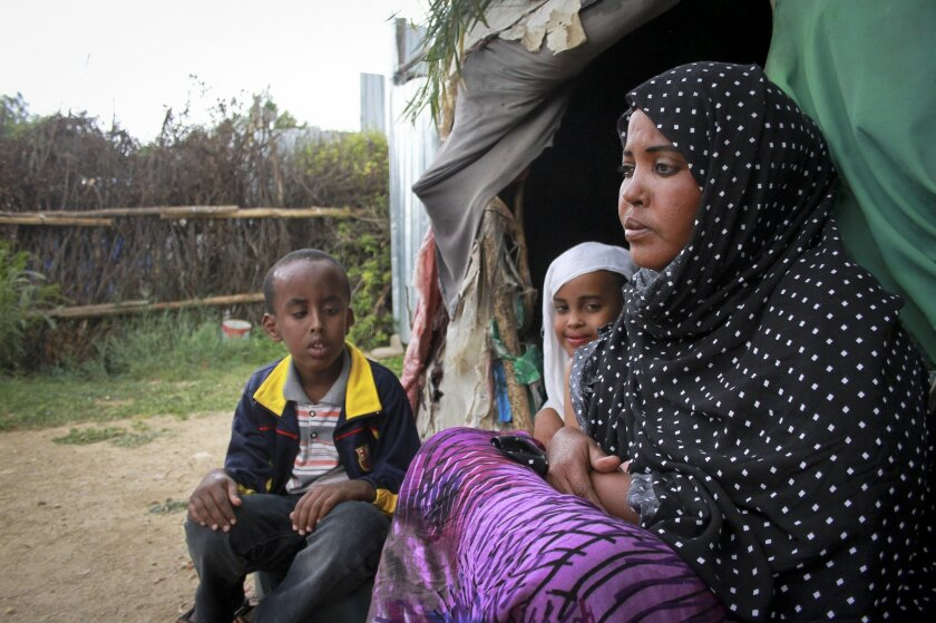 In this photo taken Sunday, April 27, 2014, Ubah Mohammed Abdule, 33, right, sits with her son Abdullahi Yusuf Ahmed, 8, left, and daughter Neshad Yusuf Ahmed, 5, center, outside her hut in the Shedder refugee camp near the town of Jigjiga, in far eastern Ethiopia. The Somali mother's home is a small shelter with a frame of sticks covered by ragged blankets on the dusty grounds of a refugee camp but it was to her that her 15-year-old son Yahya Abdi wanted to travel to on an impossible journey as a stowaway on a plane from California. (AP Photo/Elias Asmare)