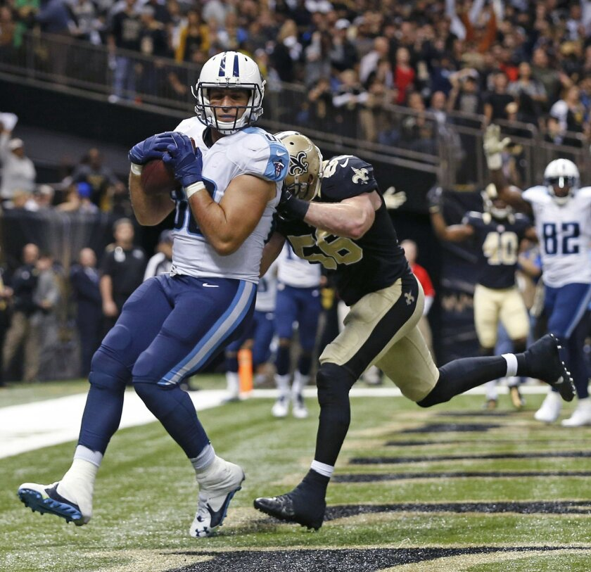 Tennessee Titans tight end Anthony Fasano (80) pulls in the game winning touchdown as New Orleans Saints linebacker Michael Mauti (56) pursues during overtime of an NFL football game in New Orleans, Sunday, Nov. 8, 2015. The Titans won 34-28. (AP Photo/Butch Dill)