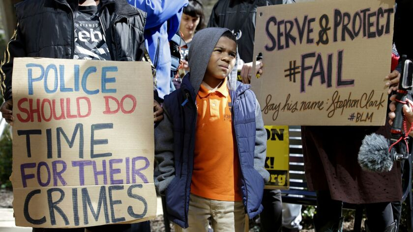 A boy joins others at a demonstration outside Sacramento City Hall in March 2018 to protest the shooting of Stephon Clark by a pair of Sacramento police officers.