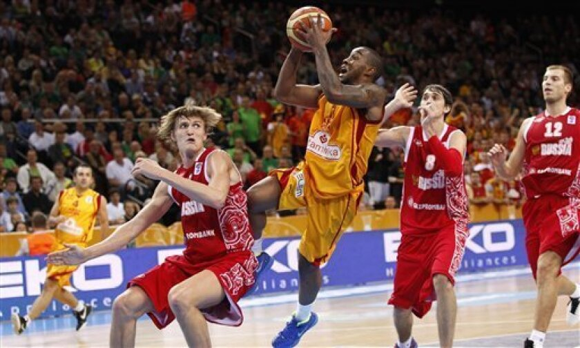Bo McCalebb, center, of  Macedonia is challenged by Andrei Kirilenko, left, from Russia during the EuroBasket 2011, European Basketball Championships bronze match in Kaunas, Lithuania, Sunday, Sept. 18, 2011. (AP Photo/Mindaugas Kulbis)