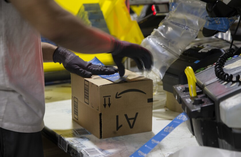 A worker tapes a box while packing items at the Amazon Fulfillment Center in San Bernardino.