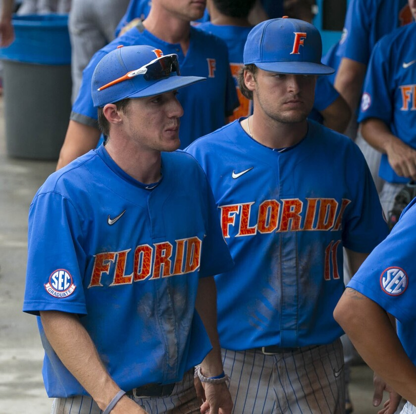 Florida's Jacob Young (1) and Nathan Hickey (11) react following to the Gators 19-1 loss to South Alabama in an NCAA regional tournament college baseball game against South Alabama at Florida Ballpark, Saturday, June 5, 2021, in Gainesville, Fla. (Cyndi Chambers/Ocala Star-Banner via AP)