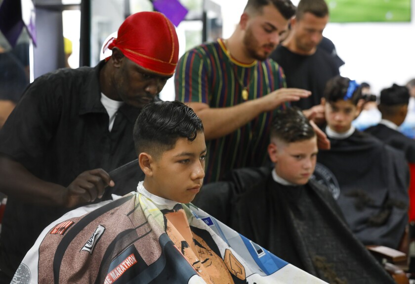 Ramses Del Rio, 12, has his hair styled by Brian Smith as the Larry Himmel Neighborhood Foundation hosted its Back-to-School Haircut event at the California Barber and Beauty College. In the background (center) Robert Farnsworth, 11, has his hair trimmed by Savan Hanna and Jeremy Pineda has his hair styled by Brian Smith.