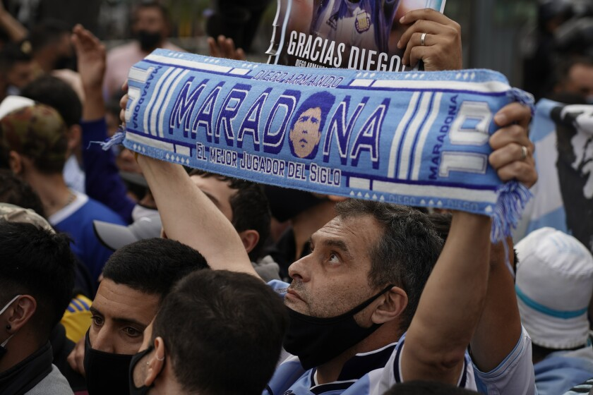 A man holds up a Diego Maradona scarf outside the presidential palace in Buenos Aires.
