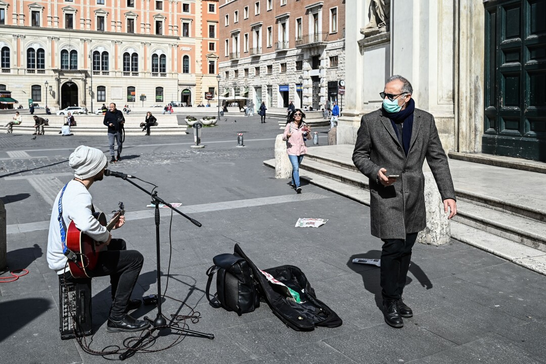 ITALY: A man wearing a respiratory mask as a precautionary measure against the coronavirus walks past a street musician as people sit at a safe distance from one another, in the background, on Piazza San Silvestro in downtown Rome.