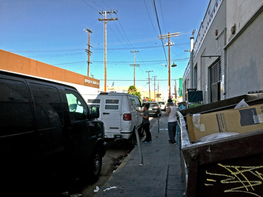 A van parked on 21st street in downtown Los Angeles cashes checks for garment workers and takes a 1% fee.