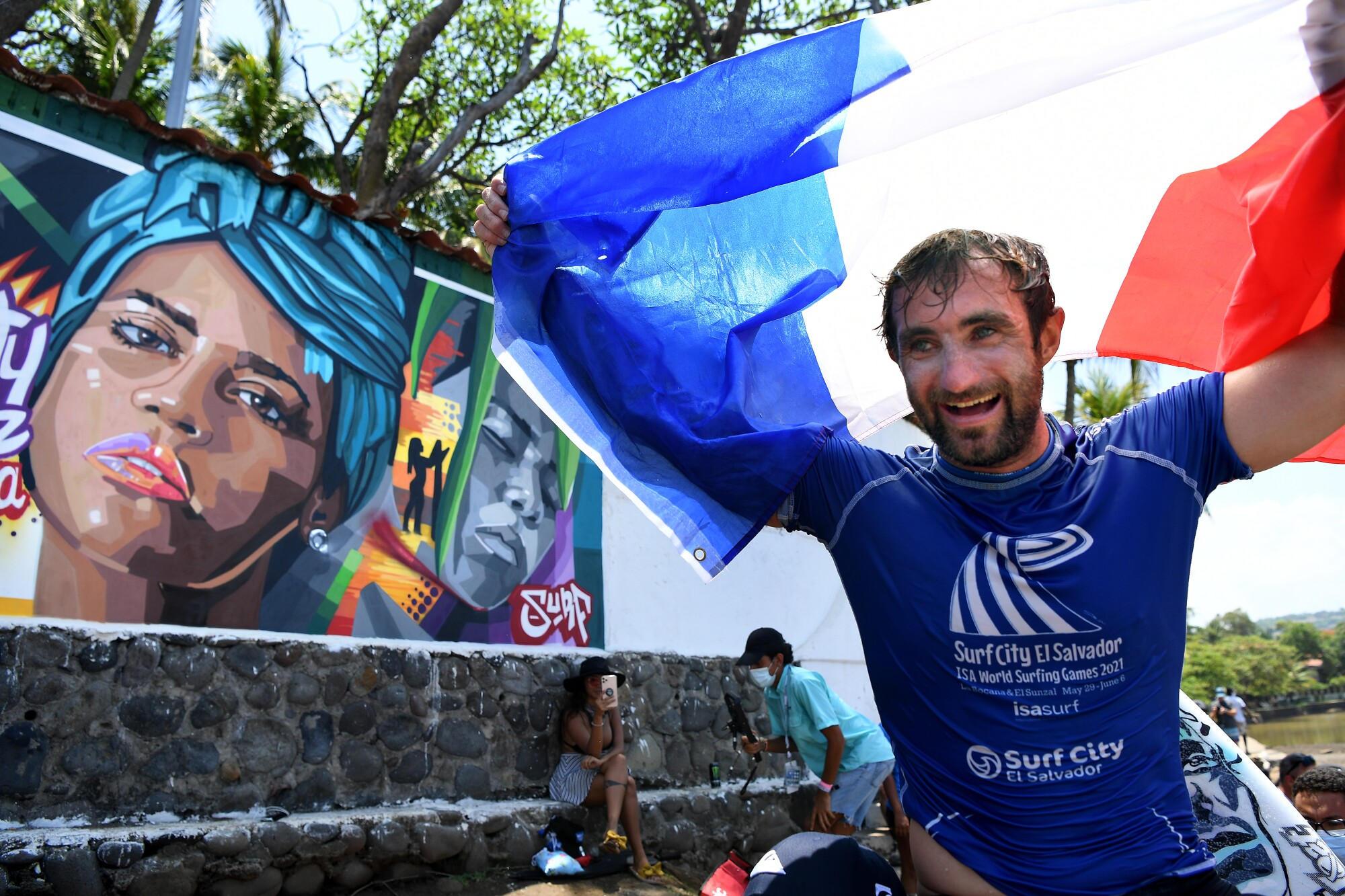 French surfer Joan Duru celebrates as he is carried past a mural of the late fellow surfer Katherine Díaz