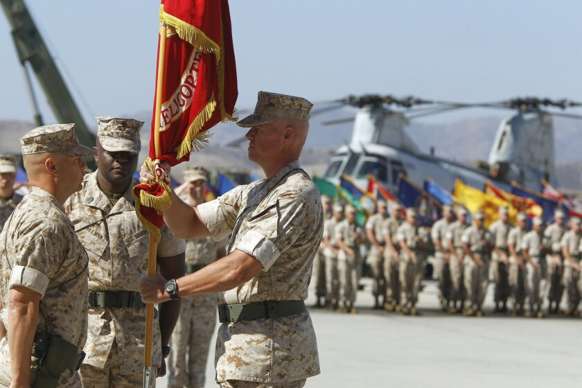 With a Marine CH-46 helicopter in the background, Lt. Col. John Field hands the HMM 364 colors to Lt. Col. Paul Kopacz during a change of command ceremony that redesignates the CH-46 squadron to the VMM 364 Osprey squadron, which Kopacz will be in command of, at Camp Pendleton on Thursday.