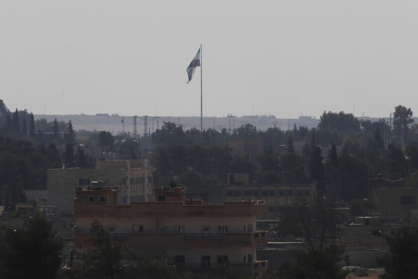 In this photo taken Oct. 23, 2019, from Akcakale, Turkey, the Syrian opposition flag can be seen across the border in Tal Abyad, Syria.