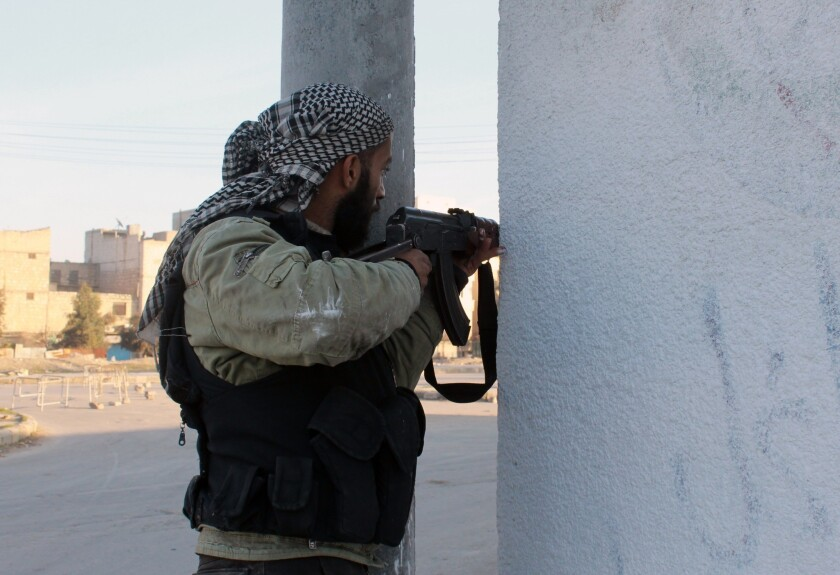 An opposition fighter guards a position in the northern Syrian city of Aleppo during clashes with the extremist Islamic State of Iraq and Syria.