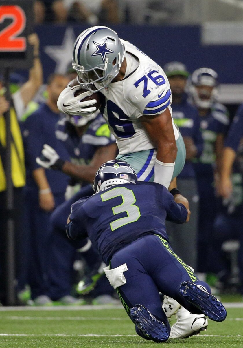 Seattle Seahawks' Russell Wilson (3) tackles Dallas Cowboys' Greg Hardy who intercepted  a pass from Wilson in the second half of an NFL football game Sunday, Nov. 1, 2015, in Arlington, Texas. (AP Photo/Brandon Wade)