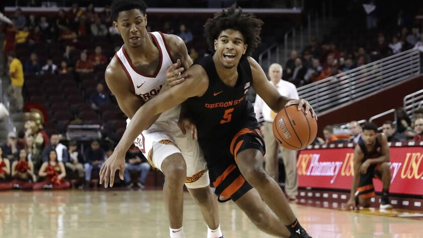 Oregon State 's Ethan Thompson, right, is defended by USC's Elijah Weaver, left, during the first half on Saturday at Galen Center.