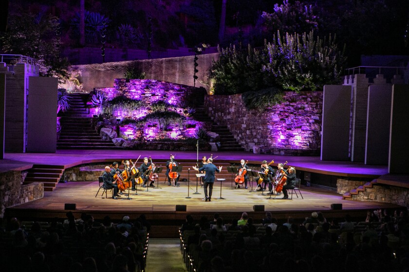 A conductor faces a semicircle of cellists on an outdoor stage.