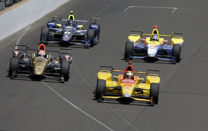 Ryan Hunter-Reay leads James Hinchcliffe, (5), of Canada, Townsend Bell (29) and Josef Newgarden into the first turn during opening laps of the 100th running of the Indianapolis 500 auto race at Indianapolis Motor Speedway in Indianapolis, Sunday, May 29, 2016. (AP Photo/R Brent Smith)