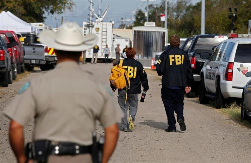 Un agente de la policía de Texas observa a dos compañeros del FBI mientras se dirigen a la iglesia baptista de Sutherland Springs, en Texas (Estados Unidos), donde un total de 26 personas murieron cuando asistían a un servicio dominical. EFE/ARCHIVO