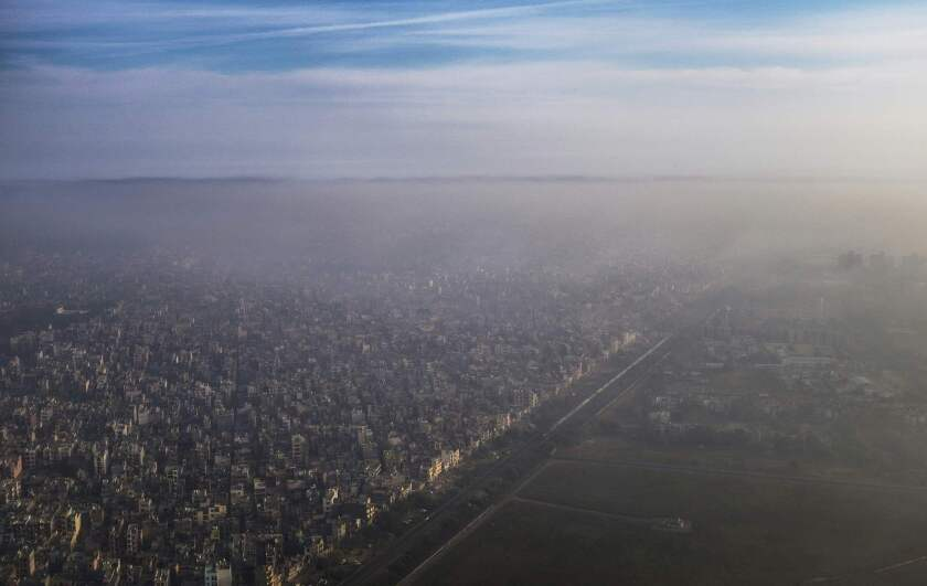 A blanket of smog extends over a densely populated neighborhood adjacent to the main airport in New Delhi on March 15, 2016.
