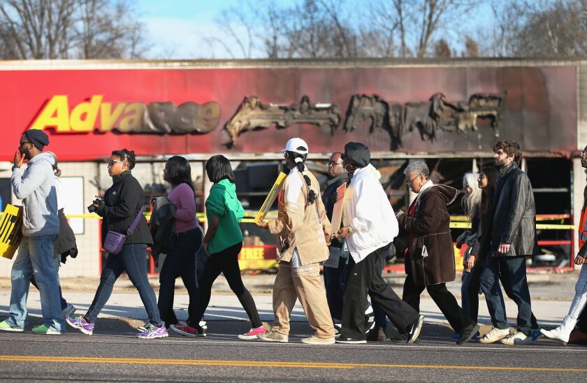 NAACP members and supporters pass by an auto parts store in Ferguson, Mo., that was destroyed by rioters as they walk Saturday on the first day of a planned seven-day, 120-mile march to the governor's mansion in Jefferson City, Missouri's capital.
