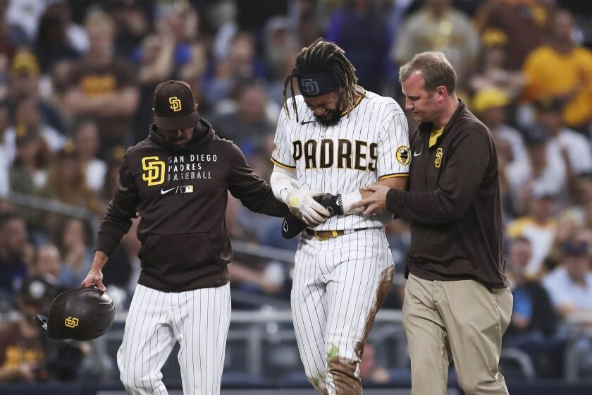 Fernando Tatis Jr., el campocorto dominicano de los Padres de San Diego, es ayudado a salir del juego