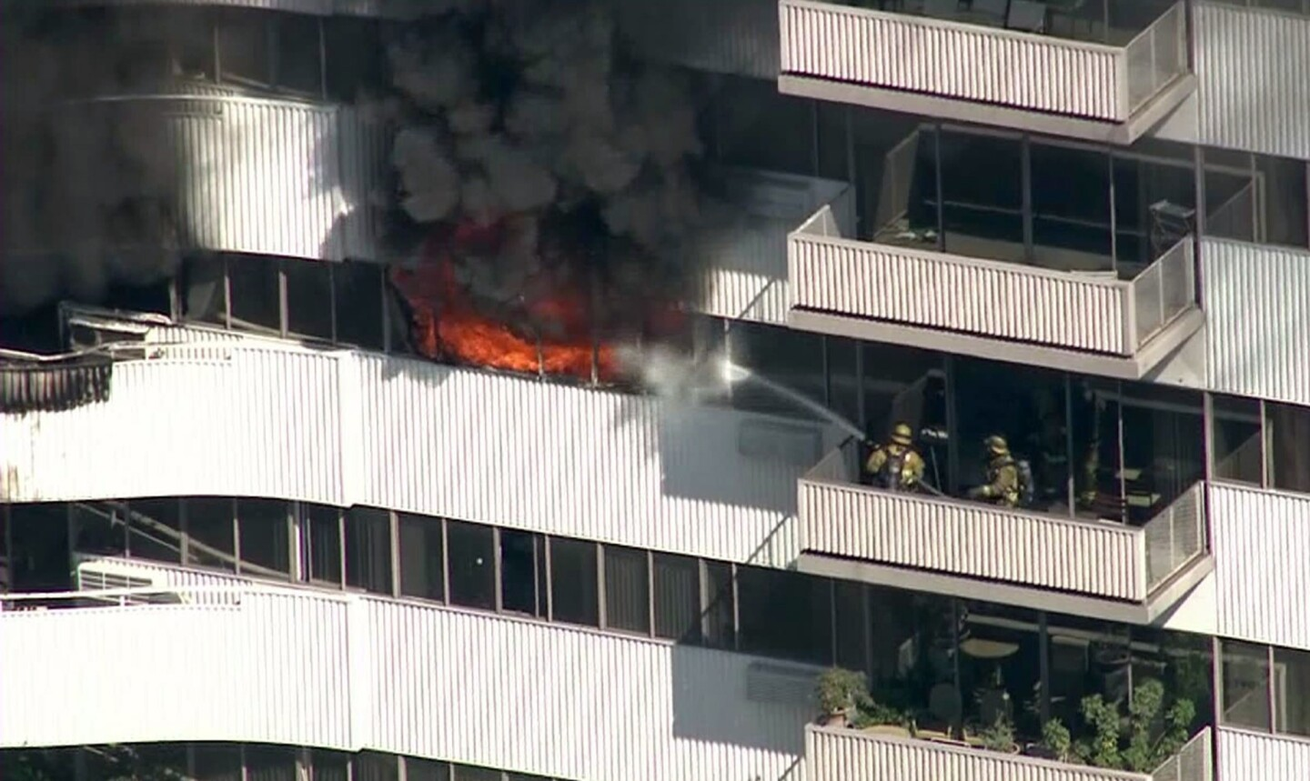 A fire burns on the 11th floor of the Barrington Plaza apartments. L.A. fire officials said the building, in the 11700 block of Wilshire Boulevard, is not equipped with a sprinkler system because it was built 52 years ago and does not fall under state regulations adopted in 1974 that require buildings taller than 75 feet to include such fire-suppression systems.