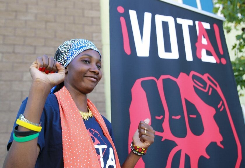 Famo Musa, 26, who is a student at Grossmont College, poses as someone takes a picture of her next to a banner encouraging young people to register to vote during the Youth Power Summit at Lincoln High School in San Diego on Saturday.