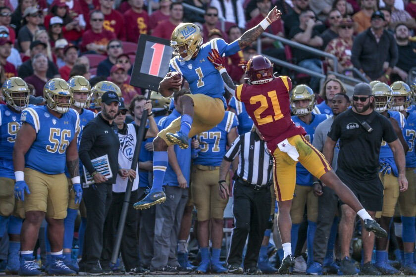 UCLA quarterback Dorian Thompson-Robinson is shoved out of bounds by by USC safety Isaiah Pola-Mao at the Coliseum on Saturday.