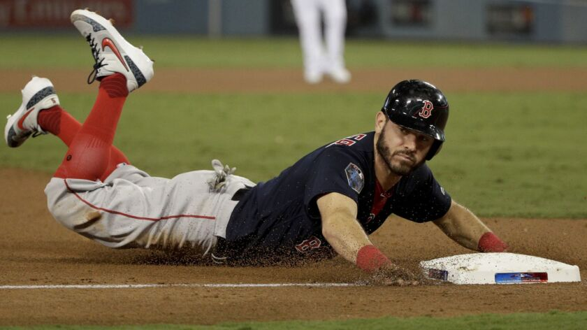 Boston Red Sox's Ian Kinsler slides safely into third during the ninth inning in Game 3 of the World