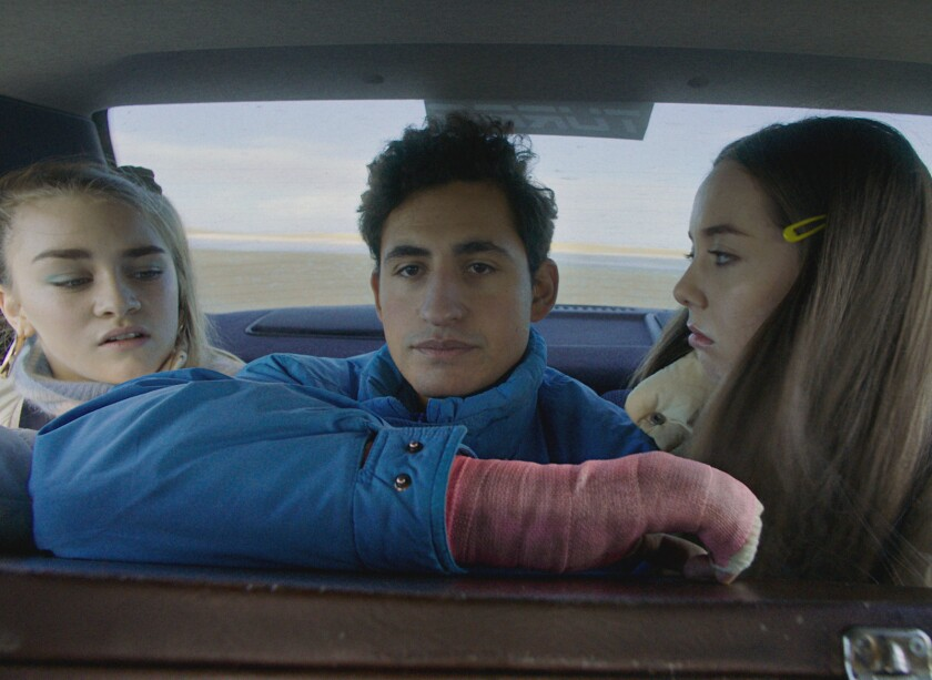 A young man wearing a pink cast sits between two girls in the backseat of a car.