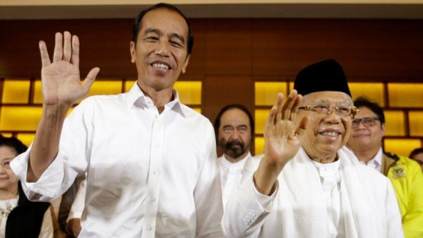 Indonesian President Joko Widodo, left, and his running mate, Ma'ruf Amin, wave at a news conference in Jakarta after polls closed in the April 17 election.