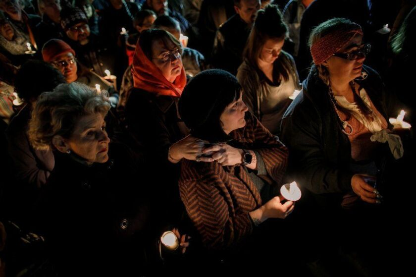 Community members attend a vigil Thursday for the four people killed Sunday.