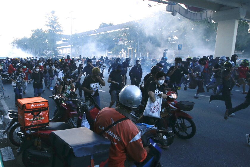 Riot police launch tear gas at anti-government protesters during a protest near Government house in Bangkok, Thailand, Monday, Aug. 16, 2021. Protesters demanded the resignation of Prime Minister Prayuth Chan-ocha for his failure in handling the COVID-19 pandemic. (AP Photo/Anuthep Cheysakron)