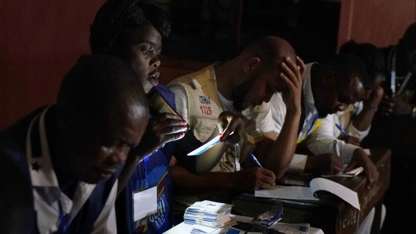Electoral commission officials tally the presidential ballots in Kinshasa, Sunday Dec. 30, 2018. For
