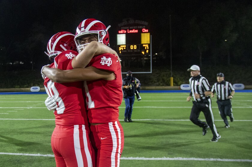 Mater Dei's Jack Ressler and Isaiah Lopez hug on the field while referees walk behind them.