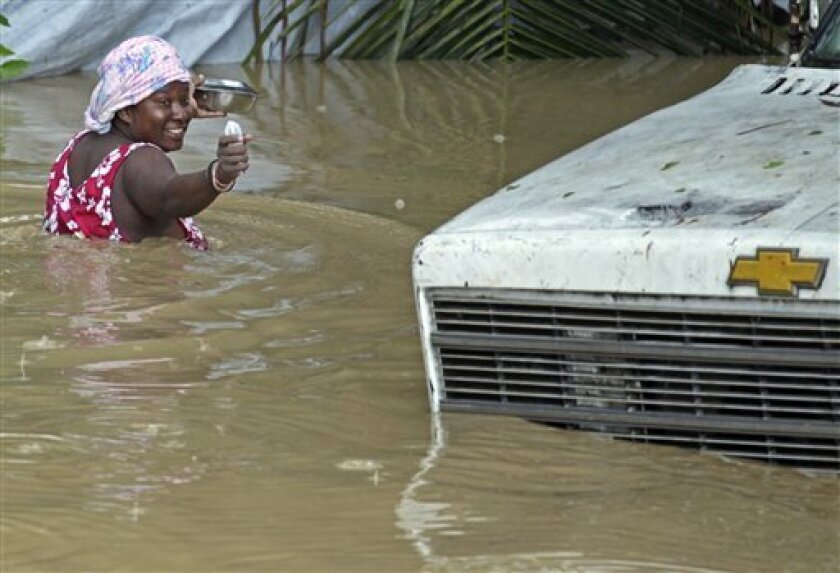 A resident of Leogane, Haiti makes her way to her home as the water level continues to rise Friday, Oct. 26, 2012.  Residents of Leogane have had five consecutive days of rain in the aftermath of Hurricane Sandy, which caused serious flooding and claimed at least 26 lives in the impoverished countr