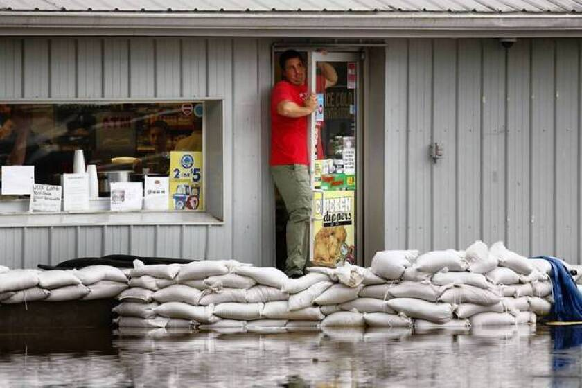Gulf residents like those in Holden, Miss., headed back to work though water remained stubbornly high.