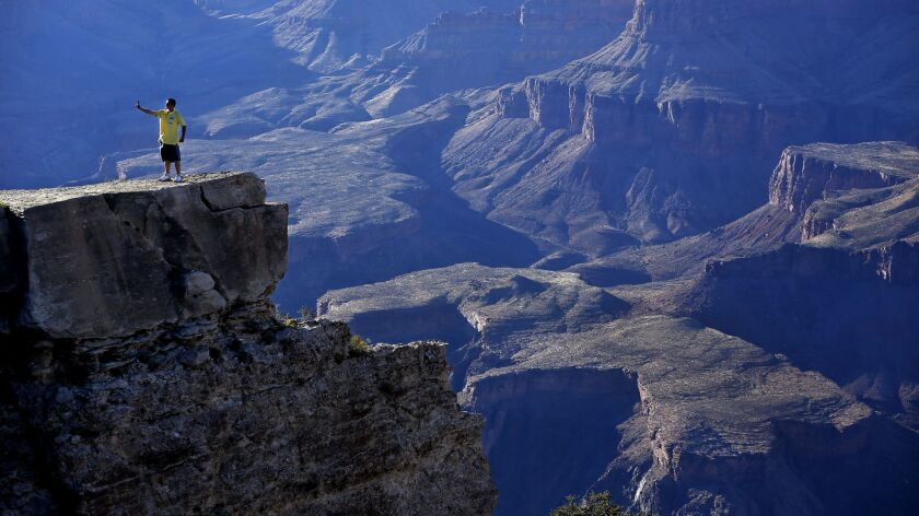 "A tourist takes a ""selfie"" photograph on a cliff located above the Grand Canyon in Grand Canyon, Ariz. on June 27, 2014."
