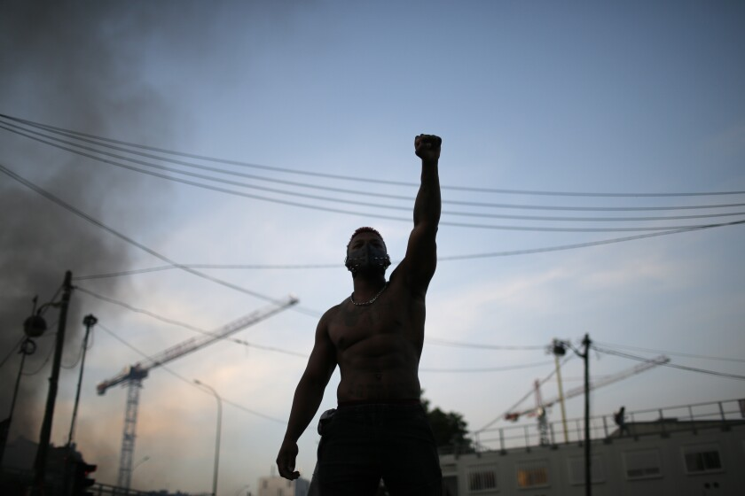 A protester raises his fist during a demonstration Tuesday, June 2, 2020. Paris riot officers fired tear gas as scattered protesters threw projectiles and set fires at an unauthorized demonstration against police violence and racial injustice. Several thousand people rallied peacefully for two hours around the main Paris courthouse in homage to George Floyd and to Adama Traore, a French black man who died in police custody. (AP Photo/Rafael Yaghobzadeh)