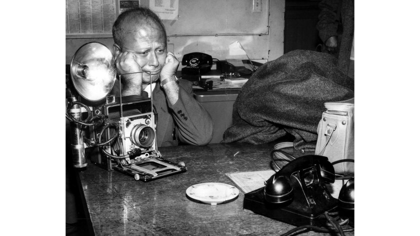 Aug. 23, 1954: Los Angeles Mirror photographer George Lacks portrays frustration after a narcotics suspect huddled under a blanket refused to come out and have his picture taken at the Central Police Station.