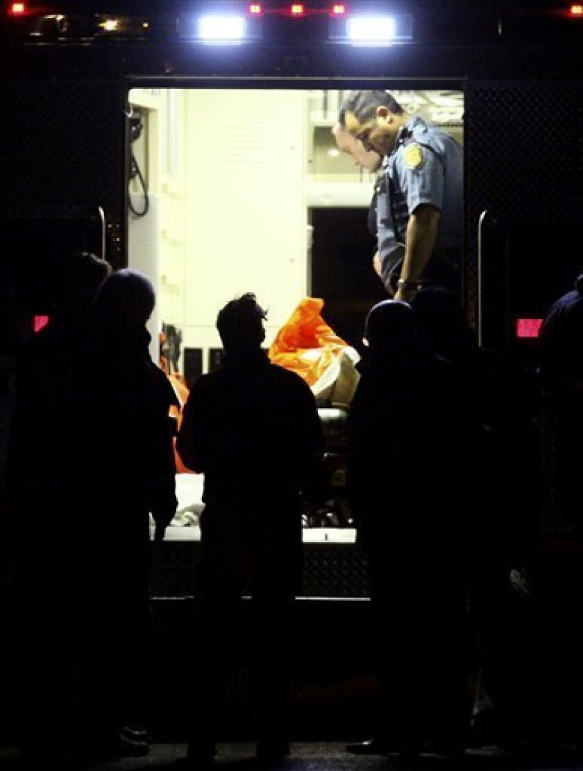 Police officers look over the body of the suspected Lakewood, Wash. police killer Maurice Clemmons, in the back of a medic unit in Seattle after he was shot and killed by a lone Seattle patrolman, Tuesday, Dec. 1, 2009. Clemmons is suspected of shooting and killing four Lakewood police officers as they sat in a Parkland, Wash. coffee shop on Sunday. (AP Photo/Seattlepi.com, Joshua Trujillo)