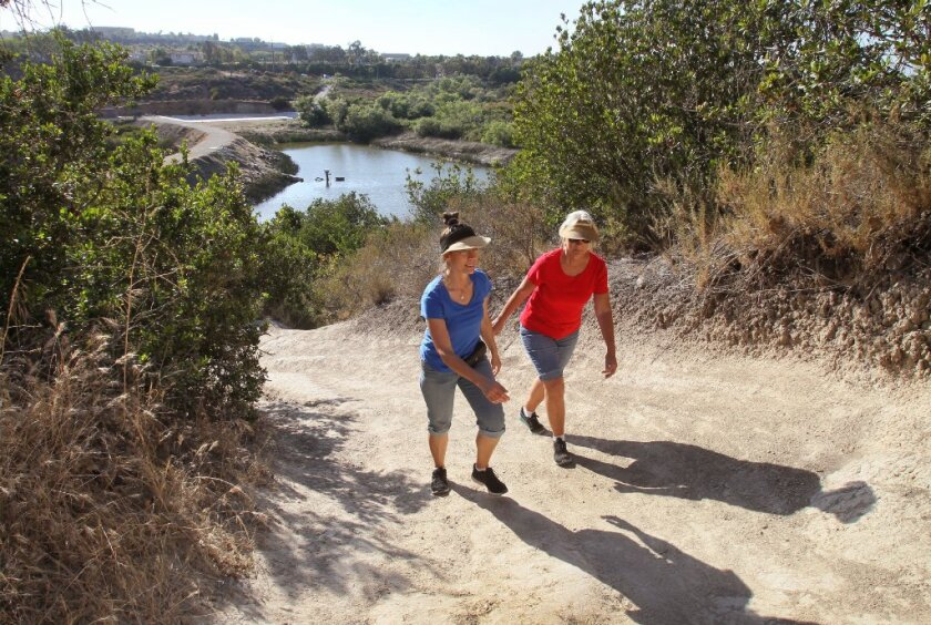 Two friends climb a steep trail near Lake Calavera in Carlsbad.