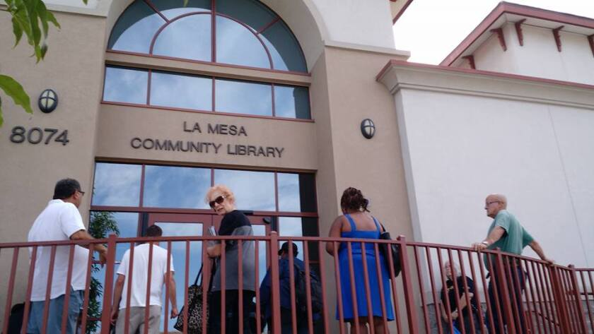 La Mesa library patrons wait to get into the building in this file photo. The city had to pay the county $745,000 as part of an agreement made regarding the building of a new library for La Mesa that has not yet happened.